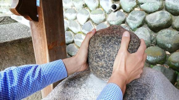 Holding Omokaru no Ishi (heavy or light stone)